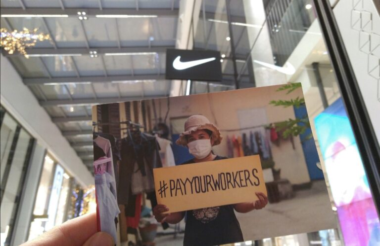 Postal de la campaña Pay Your Workers ante una tienda de NIKE, para exigir a la marca que pague a sus trabajadoras